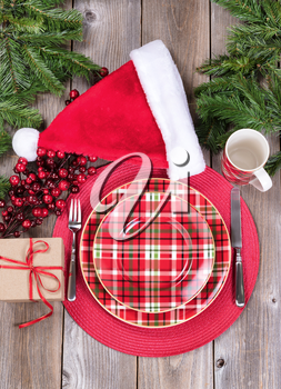 Overhead view of a festive Christmas dinner setting with red berry decorations, Santa cap, evergreen branches and present on top of rustic wood