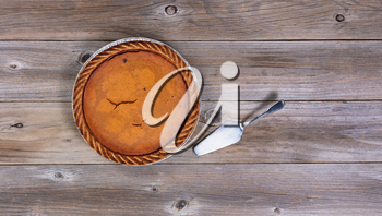 Overhead view of Pumpkin pie and spatula server on rustic table