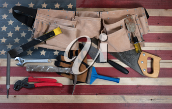 Labor Day background with USA rustic wooden flag and used industrial tools plus utility belt