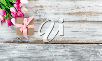overhead view of a pink springtime tulips and brown gift box on white weathered wooden boards