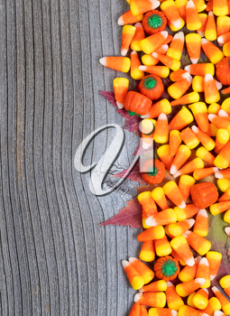 Close up of Halloween candy with autumn leaves on rustic wooden boards