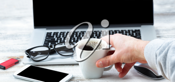 Close up of male hand holding a cup of fresh coffee with workstation technology in background for business or education use