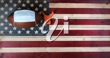 American football with surgical protective mask and kicking tee on vintage United States wooden flag background. Coronavirus concept for affect football sports with copy space