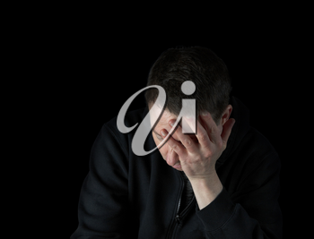 Depressed mature man holding his face in the darkness while dressed in a black sweater