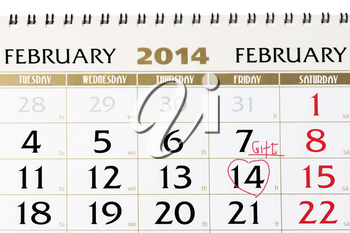 Calendar page with red heart on February 14 2014. Closeup.