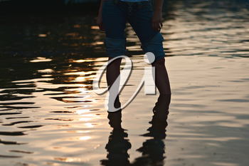 Female legs in rolled jeans in sea water on soft background of setting sun.