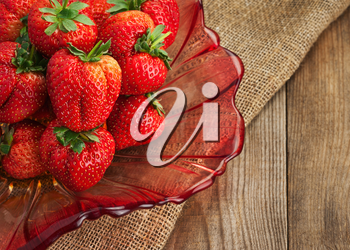 Fresh ripe strawberries in glass bowl on wooden background. Closeup.