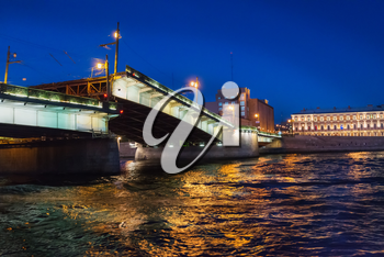 Night view of illuminated drawbridge (Foundry Bridge) on night river Neva water, one of the most familiar images of the Northern capital of Russia, Saint Petersburg.
