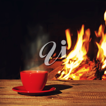 Red cup of tea or coffee near fireplace on wooden table. Winter and Christmas holiday concept. Photo with retro filter effect.