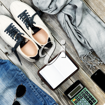 Set of travel items including scarf, sunglasses, sneakers, note book, calculator and phone. Overhead view. Flat lay.
