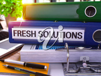 Blue Ring Binder with Inscription Fresh Solutions on Background of Working Table with Office Supplies and Laptop. Fresh Solutions Business Concept on Blurred Background. 3D Render.