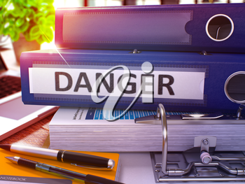 Blue Ring Binder with Inscription Danger on Background of Working Table with Office Supplies and Laptop. Danger - Toned Illustration. Danger Business Concept on Blurred Background. 3D Render.