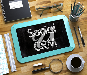 Social CRM - Text on Small Chalkboard.Social CRM Handwritten on Mint Chalkboard. Top View Composition with Small Chalkboard on Working Table with Office Supplies Around. 3d Rendering.