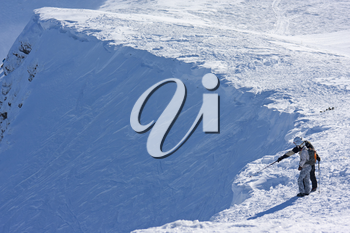 Two ski freeriders are standing on the brink of a precipice.