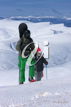 Two backcountry snowboard-freeriders are going uphill.