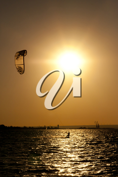 Sepia-toned photo of the evening sun and the kite-surfer sliding on the water