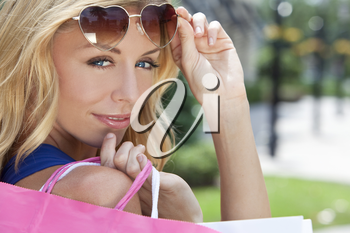 Beautiful, happy and fashionable woman with colorful pink and white shopping bags and wearing heart shaped sunglasses
