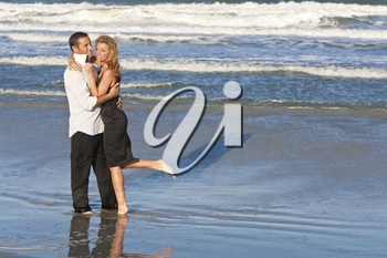 A young man and woman embracing as a romantic couple on a beach