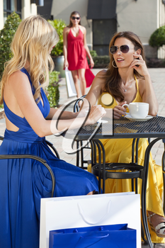 Two beautiful and sophisticated young women friends wearing sunglasses and having coffee around a modern city cafe table surrounded by shopping bags with their friend joining them in the background