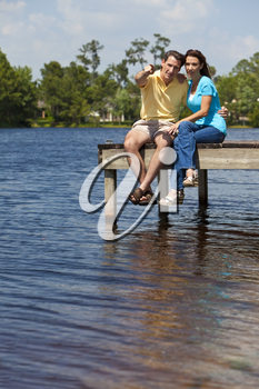 Portrait shot of an attractive and happy middle aged man and woman couple in their thirties, sitting together on a pier by a lake and pointing.