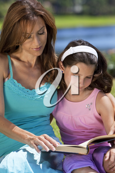 Woman and girl, mother and daughter, reading a book together outside in the countryside