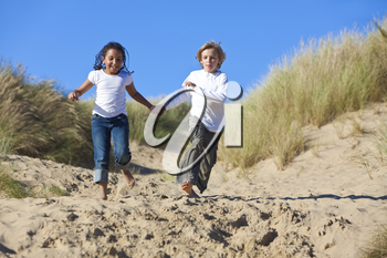 A young mixed race African American girl and a little blond boy running, holding hands and having fun in the sand dunes of a sunny beach