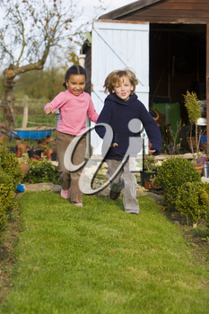 Two young children, one a blonde boy the other a mixed race girl, having fun in an Autumnal garden