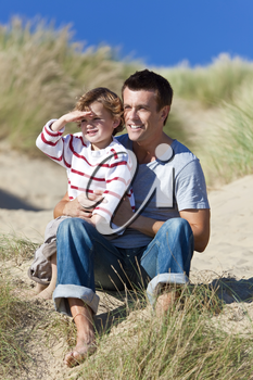 A man and young boy, father and son, sitting down and having fun in the sand dunes of a sunny beach