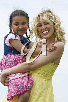 A beautiful blond haired blue eyed young woman holding on to her mixed race young daughter