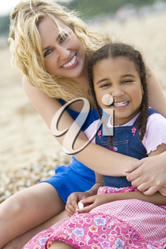 A beautiful blond haired blue eyed young woman having fun with her mixed race young daughter at the beach