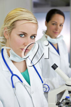 A blond female medical or scientific researcher or doctor using her microscope in a laboratory with her  colleague out of focus behind her.