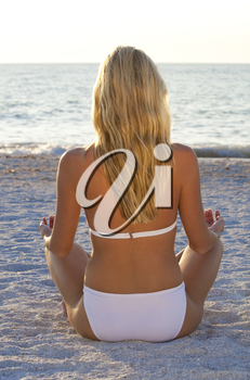 A beautiful young blond woman in a white bikini sits crosslegged on a beach at sunset