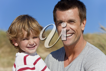 A man and young boy, father and son, together having fun on sunny day