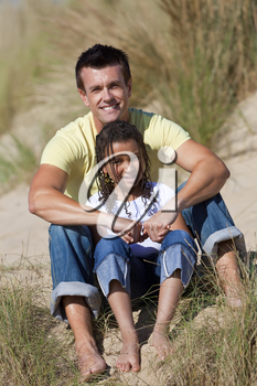 A man and young girl, father and mixed race daughter, sitting in the sand dunes of a sunny beach