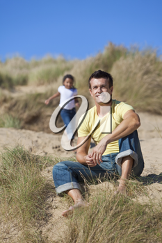 A man and young girl, father and mixed race daughter, playing and having fun in the sand dunes of a sunny beach