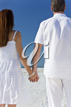 Rear view of man and woman romantic couple in white clothes holding hands on a deserted tropical beach with bright clear blue sky