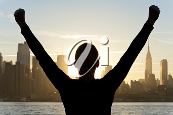Rear view silhouette of a woman celebrating arms raised at sunrise in front of the Manhattan skyline New York City, United States of America