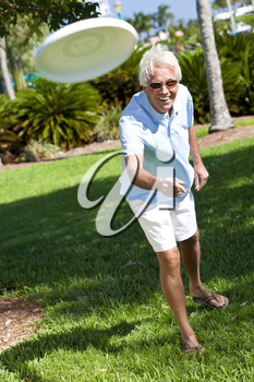 Happy senior man throwing a frisbee outside in a park in sunshine