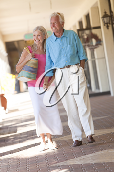 Happy senior man and woman couple holding hands and walking through a sunlit shopping mall