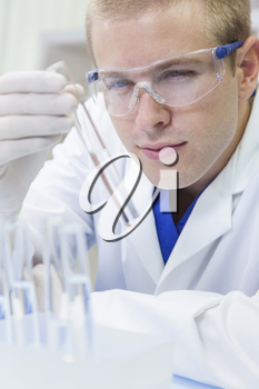 A male medical or scientific researcher or doctor looking at a test tube of clear liquid in a laboratory with microscopes.