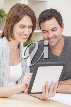 Happy man and woman couple in their thirties, sitting together at home by a table using a tablet computer