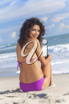 A sexy young brunette woman or girl wearing a purple bikini and ssitting on a deserted tropical beach with a blue sky