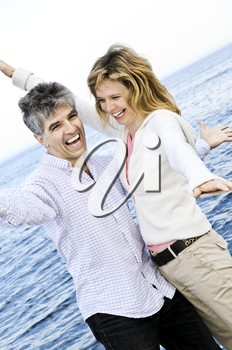 Carefree mature baby boomer couple enjoying seashore