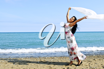 Portrait of beautiful smiling brunette girl at beach holding white scarf