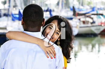 Beautiful young woman hugging boyfriend standing at harbor