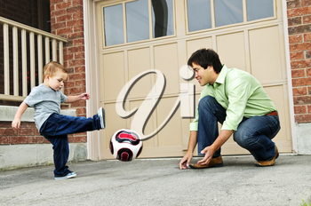 Father teaching son to play soccer on driveway