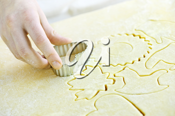 Cutting cookie shapes in rolled dough with cutter