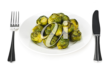 Plate of roasted green brussels sprouts with knife and fork isolated on white