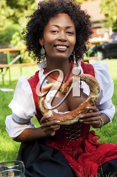Very beautiful woman of color in traditional Bavarian costume - dirndl - drinking beer and eating traditional pretzel