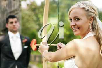 Happy wedding couple, she is 'shooting' her guy with a bow and a heart shaped arrow like Amor, the roman God of love